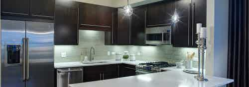AMLI River North penthouse kitchen with two candle sticks on a quartz counter and dark wood cabinets visible in the back