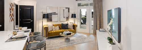 Interior view of AMLI Quadrangle living room with balcony doors and light hardwood with an elegant retro decor style