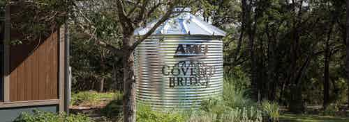 AMLI Covered Bridge apartment community sign on a water tank nestled between tall green trees