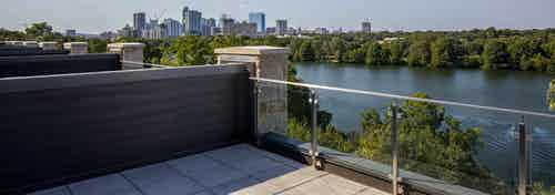Daytime view of tree lined lake and downtown Austin skyline from 4th floor deck of AMLI South Shore lakefront apartment home