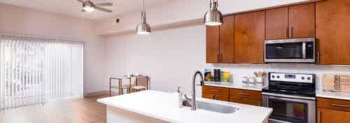 A renovated kitchen and dining room at AMLI Park Avenue apartments with an island and with dining room table and sliding door
