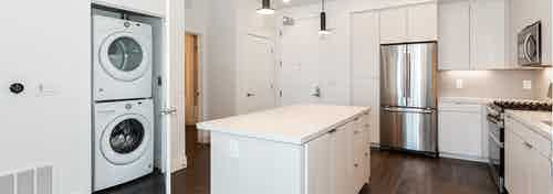Interior of AMLI Park Broadway apartment kitchen with white cabinetry, stainless steel appliances and full washer and dryer