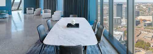 AMLI Fountain Place sky lounge with large white table with 6 chairs next to wall of windows with 4 white chairs in rear