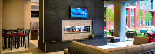 An outdoor fireplace at AMLI Denargo Market apartments with couches and a television with a slight  view of the pool area