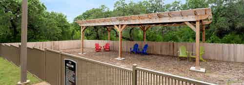 AMLI Covered Bridge's second dog park with a wood chipper floor, wooden shade arch, and colorful lounge seating
