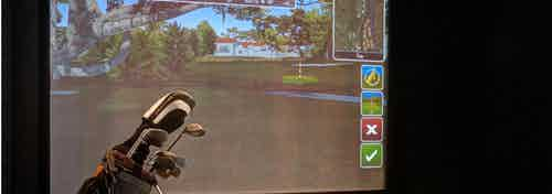 Golf simulator at AMLI River North apartment community showing a virtual golf course for residents to experience