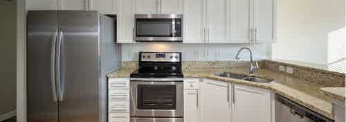 Close up of AMLI Lindbergh apartment kitchen with white cabinets, granite countertops, and stainless steel appliances