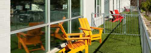 Exterior close up of a small fenced in apartment yard at AMLI South Shore with green turf and two orange lounge chairs