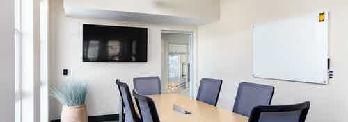Interior view of private conference room at AMLI Littleton Village apartments with big screen TV and frameless white board