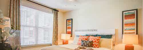 A bedroom at AMLI Interlocken apartments with lamps and two pieces of artwork with window views of the adjacent building
