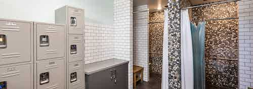 Interior of boat house bathroom showers with pebble tile accent walls and storage lockers at AMLI Marina Del Rey apartments