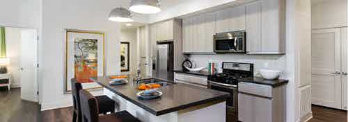 AMLI Lex on Orange apartment kitchen with light cabinetry, stone designer backsplash with quartz countertops and appliances