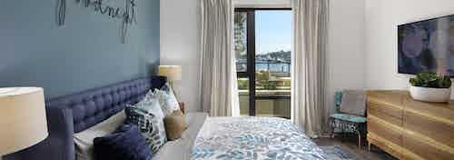 Interior view of AMLI Marina Del Rey bedroom with blue upholstered queen headboard, big screen TV and window facing marina
