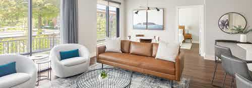 Guest suite with brown leather couch and two white chairs and coffee table near large windows at AMLI Addison apartments