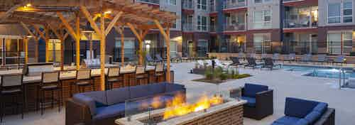 Nighttime view at AMLI Littleton Village fire pit surrounded by couches and chairs with the pool and grills in the background