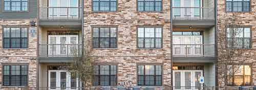 Daytime exterior video of AMLI Covered Bridge building multicolored brick façade including windows and balconies
