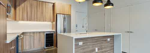 Redesigned interior of AMLI on 2nd kitchen with modern multi toned wooden cabinets and stainless steel appliances