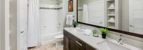 Interior of AMLI Piedmont Heights bathroom with a double dark wood vanity and mirror with a toilet and white shower tub