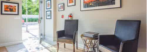 AMLI Evanston live/work interior with black leather chairs lined against creme colored walls with orange wall art