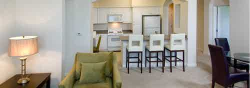 Interior view of AMLI Warner Center furnished apartment living room and kitchen with white cabinetry and white appliances