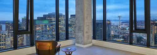 Interior view of apartment of AMLI Arc penthouse living room with floor to ceiling windows and view of Downtown Seattle
