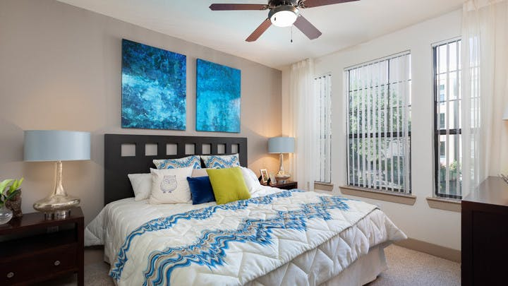 AMLI Eastside bedroom with bright windows and vibrant blue wall art hanging on a tan accent wall above a white bed