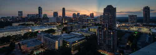 Exterior view of a gorgeous cityscape of tall buildings with varying heights after the sun has set in Atlanta at dusk