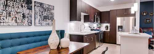 A kitchen and dining room at AMLI Cherry Creek apartments with an island and a dining room table and artwork on the wall