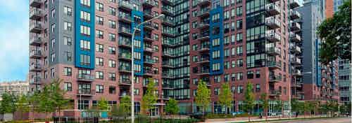 Daytime view of the AMLI Lofts apartment community building which has a pale red brick facade with vibrant blue accents