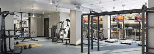 Interior of AMLI Quadrangle fitness center with various cardio and weight exercise equipment with grey flooring and tan walls