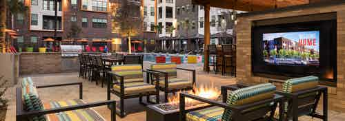 AMLI on Aldrich outdoor living area with colorful seating around a fire facing large TV with build facade in background