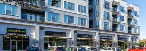 Exterior view of onsite retail shops at AMLI South Shore apartment community with outdoor umbrellas and parked cars