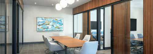 Interior view of AMLI Fountain Place conference room with table and 6 chairs surrounded by private offices with glass walls