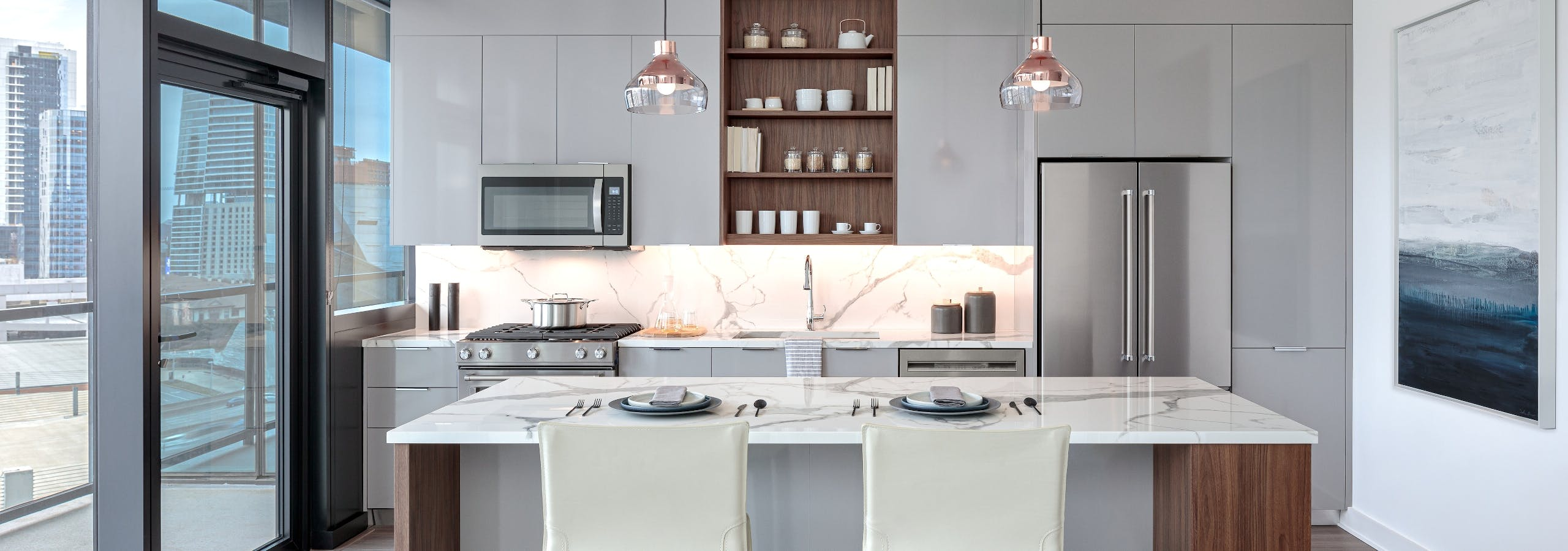 Island kitchen with stainless steel appliances, pendant lights & scenic balcony