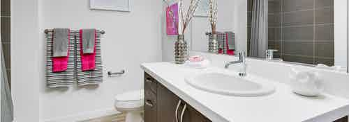 Bathroom at AMLI Cherry Creek apartments with a white counter top and white walls with a stainless steel fixtures and mirror
