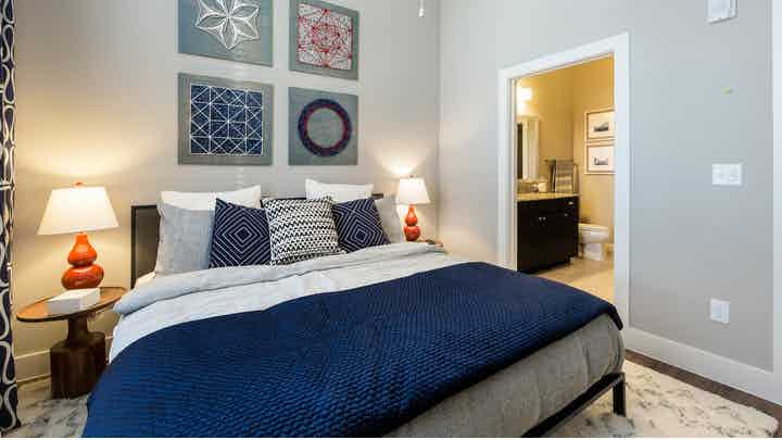 Interior view of AMLI Campion Trail bedroom area with bed with dark blue sheets and pillows and night stand