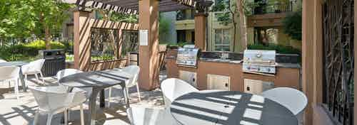 Pergola shade canopy over spacious outdoor grilling station with three dining tables at AMLI Warner Center apartment building