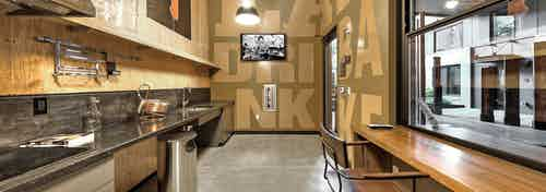 Interior of cooking lab for beer making at AMLI South Lake Union high wooden wall ceilings sink and stove and tv on wall