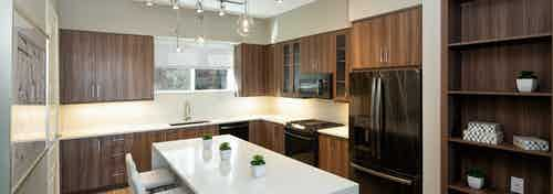 AMLI South Shore island kitchen with a built in dark wood shelf and cabinets with quartz countertops and white barstools