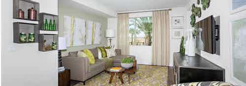 Interior of AMLI Spanish Hills apartment living room with sofa facing big screen TV and large window with sheer tan curtains