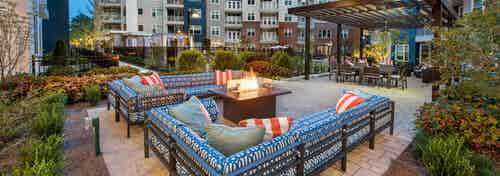 Two patterned blue L couches with a fire pit in the center and green foliage surrounding the patio area at AMLI Buckhead