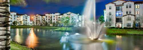 Nighttime exterior view of AMLI Doral apartment buildings surrounding a lake with a water fountain in the center