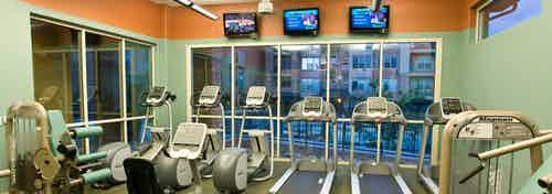 Fitness center at AMLI Inverness apartments with multiple treadmills and elliptical machines and televisions and windows