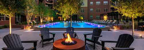 Evening view of AMLI Grapevine dark orange poolside fire pit with black surrounding seating and the pool in the background