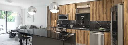 Interior view of AMLI Midtown Miami apartment kitchen with dark marble island and zebra wood cabinets and living room at left
