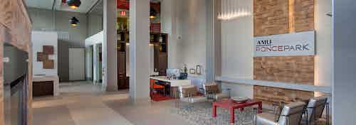 Interior of leasing office at AMLI Ponce Park with high ceilings and multiple desks with seating area and a coffee bar