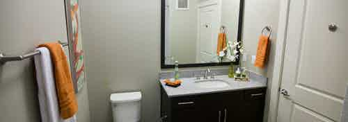 Interior view of a bathroom at AMLI Riverfront Park apartments with a sink and a large mirror and towel rack with towels