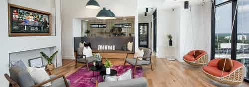 AMLI Lenox sky lounge with bright pink rug and multiple seating areas and a TV and two swings near large windows