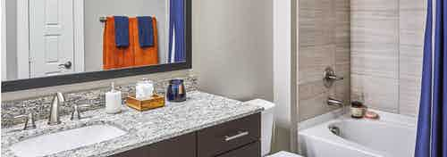 """AMLI Covered Bridge bathroom with 42"""" espresso cabinets with brushed chrome hardware and elegant granite countertop"""