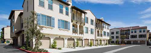Exterior daytime rendering of driveway at AMLI Spanish HIlls apartments with blue window shutters, trees and garage doors
